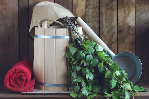 Березовый веник, деревянное ведро и банное полотенце.