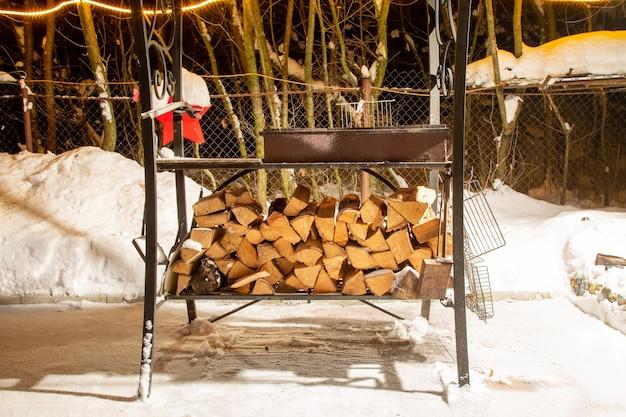 バーベキュー用に用意された白樺の薪。雪の中でグリルの下に横たわっています。冬の夜