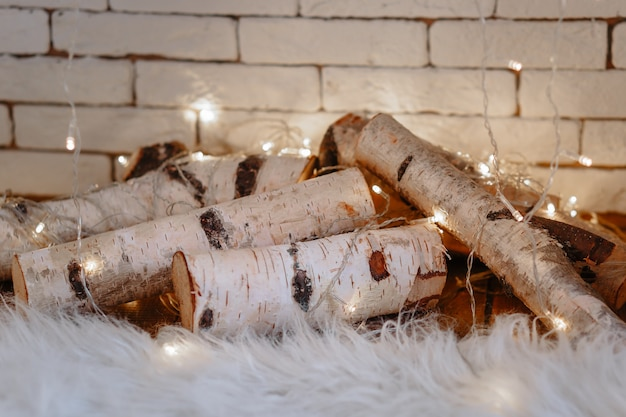 Birch logs lying in the fireplace with garland on them