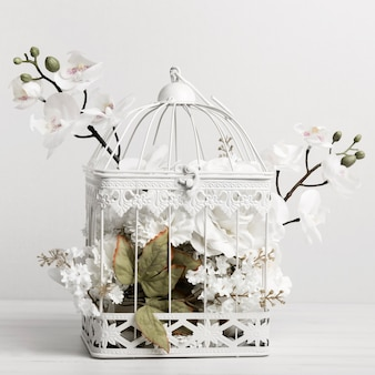 A bird cage full of beautiful flowers