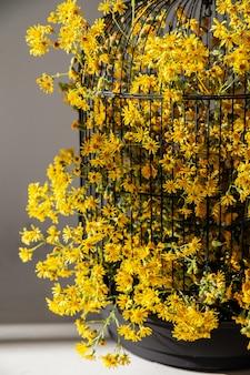가정 장식을 위한 노란색 꽃이 있는 새장 프리미엄 사진