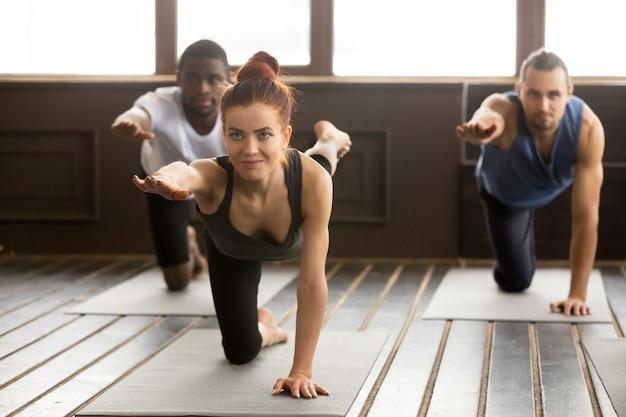 Группа спортивных людей в bird dog упражнение с инструктором