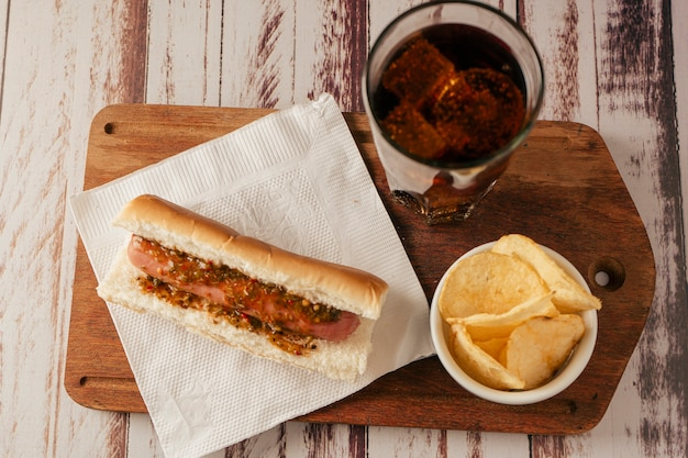 소박한 테이블에 소다와 감자 칩을 곁들인 치미추리 소스를 곁들인 핫도그의 조감도. 수평보기. 빠르고 정크 푸드 개념입니다.