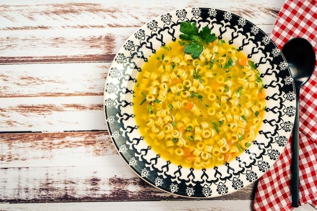 집에서 만든 작은 국수와 파슬리를 곁들인 절묘한 닭고기와 야채 수프의 조감도. 소박한 나무 테이블에 빈티지 접시에 제공됩니다. 자연 및 건강 식품 개념
