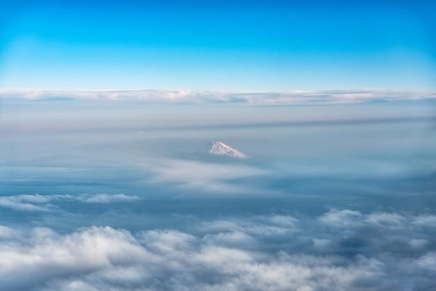Вид с высоты птичьего полета на гору фудзи, знаменитый вулкан в японии, снятый из окна самолета.