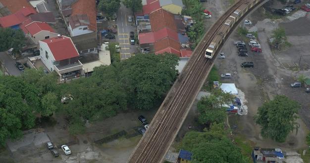 Вид с высоты птичьего полета на бедный район и поезд на железных дорогах бангкока, таиланда