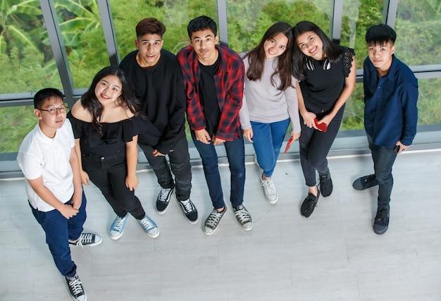 Снимок портрета с высоты птичьего полета группы из семи молодых мужчин и женщин, стоящих и смотрящих в камеру. друзья из колледжа фотографируют вместе с милой улыбкой. концепция отношений