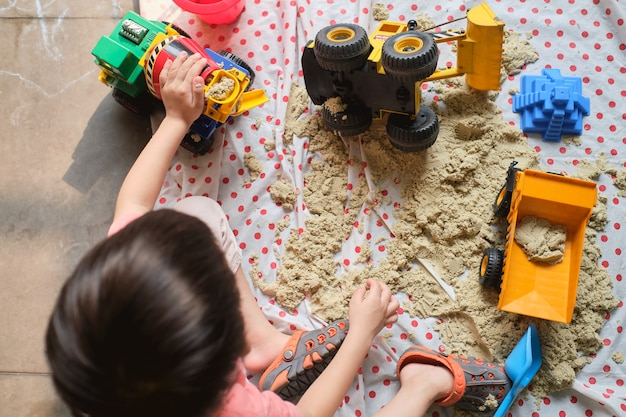 Bird eye view of toddler boy playing with kinetic sand at home, child playing with toy construction machinery, creative play for kids concept