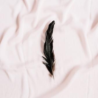 ピンクのテキスタイル表面の鳥の羽