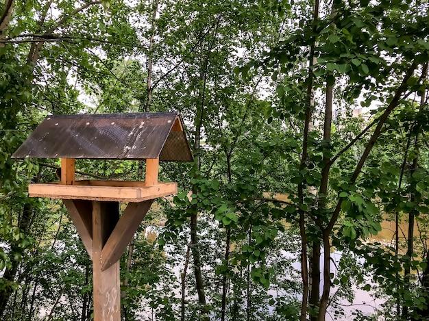 Кормушка для птиц. домик на палке для птиц, веселая квартира. простая конструкция для кормления птиц на берегу реки. приют для разведения птиц. садовая кормушка для птиц. место для текста или логотипа