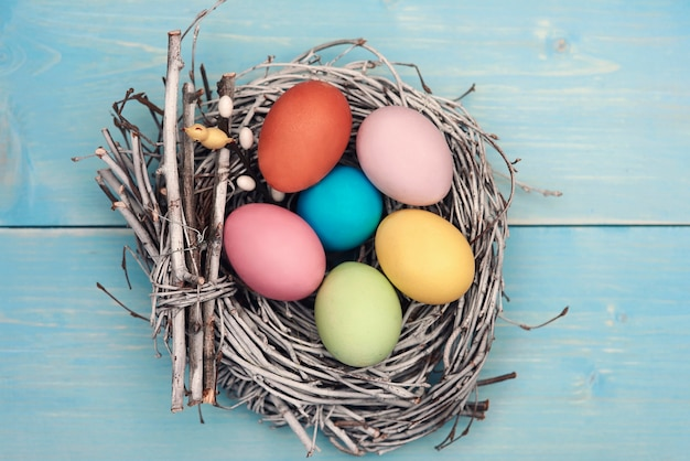 Bird nest fulfilled with pastel color eggs