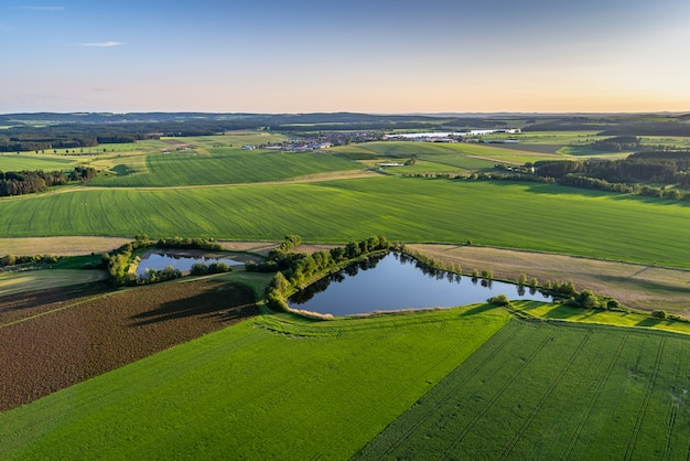 Bird's-eye shot of breathtaking green fields with small ponds in a rural area