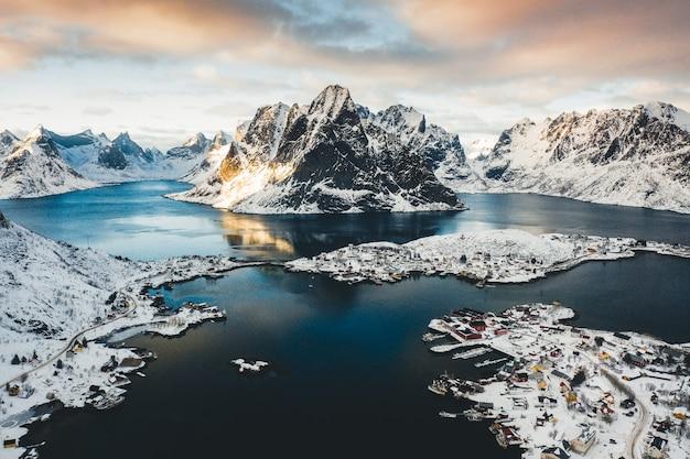 Снимок прибрежного городка с высоты птичьего полета у водоема со снежными горами