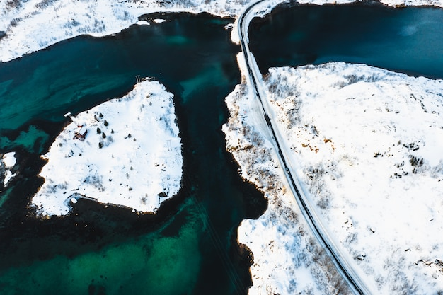 Bird's-eye shot of a road going through snowy islands on a body of water