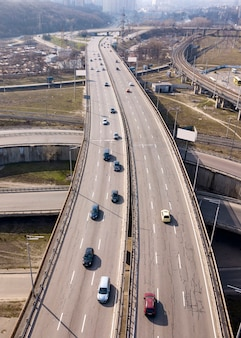 Bird's eye view from drone of speedway asphalt road, moving fast cars and tracks in a spring sunny day in city kiev, ukraine.