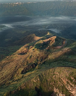 Bird's eye view of hills covered in greenery and fog under the sunlight - perfect for wallpapers