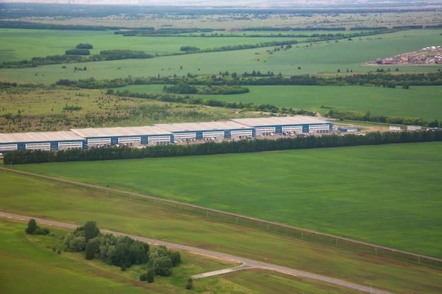 Bird's-eye view of industrial buildings among fields
