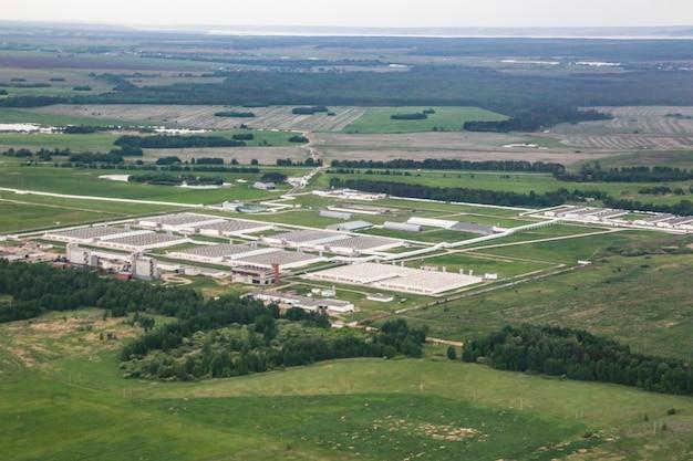Bird's-eye view of industrial buildings among green fields