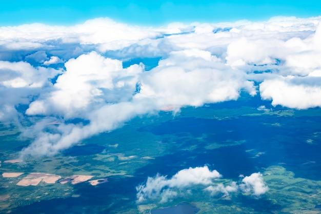 Вид с высоты птичьего полета на белые облака и зеленый деревенский пейзаж