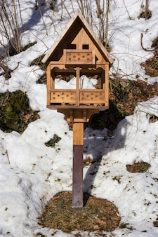 Birdhouse covered snow and snowflakes in forest