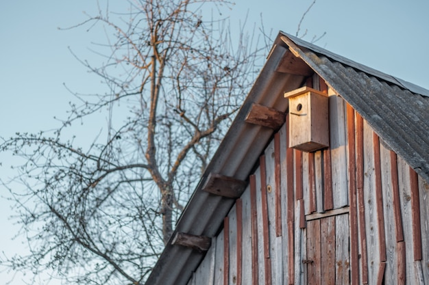 Birdhouse hanging under roof of old wooden shed next to tree against blue sky, house for birds