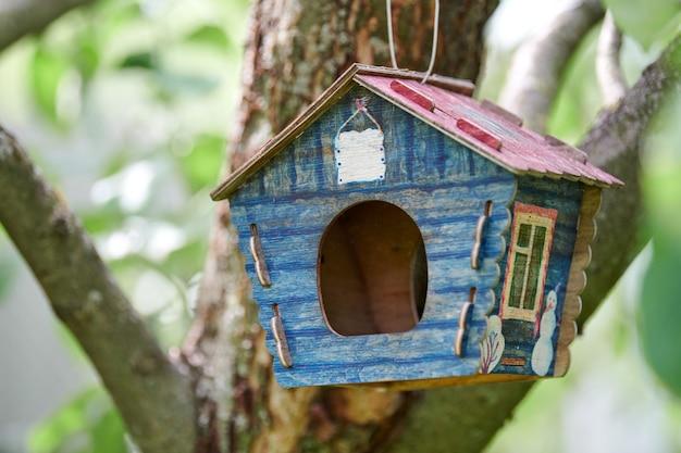 木の上の巣箱。鳥の家とリンゴの木の枝。鳥の餌のための公共公園のかわいい青い巣箱。