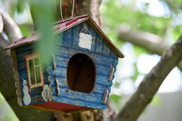 Birdhouse on tree. branch of apple tree with bird house. cute blue nest box in public park for bird feed.