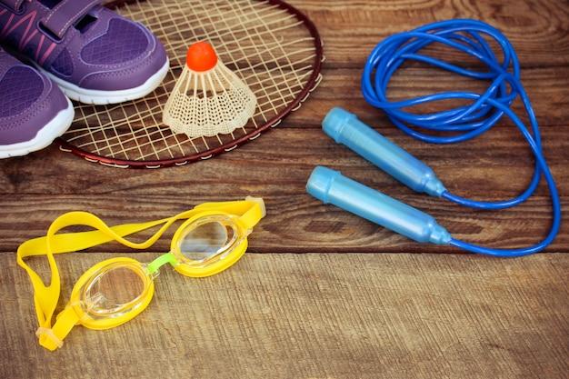 Птичка на ракетке, скакалка, плавательные очки и кроссовки на деревянном фоне.