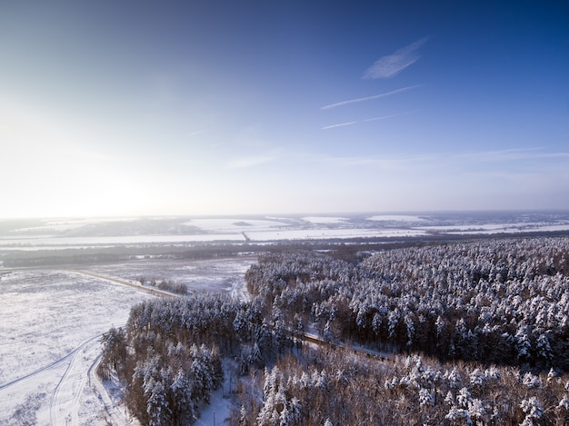Birds eye aerial view to road through winter forest frozen river on background