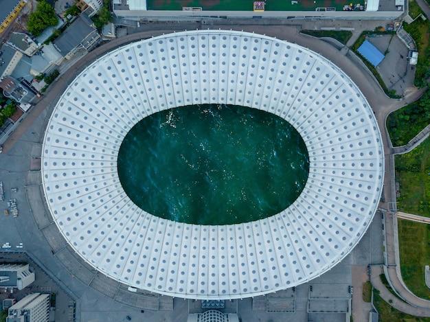 屋根の中に海のターコイズブルーの水があるサッカースタジアムのドローンからの鳥の目のパノラマビュー。上面図。