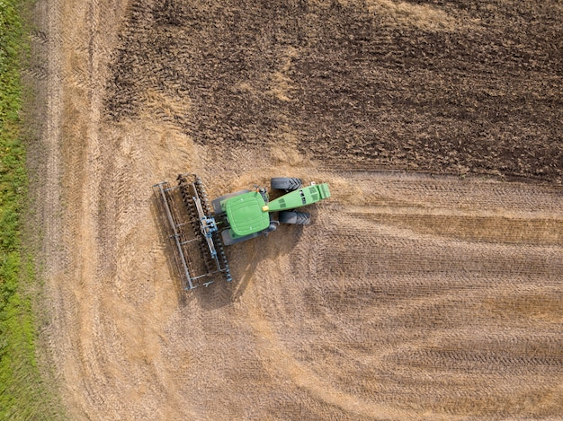 Birds eye view from the drone of the field after harvest. the tractor plows the field, preparing the soil for agricultural work. top view