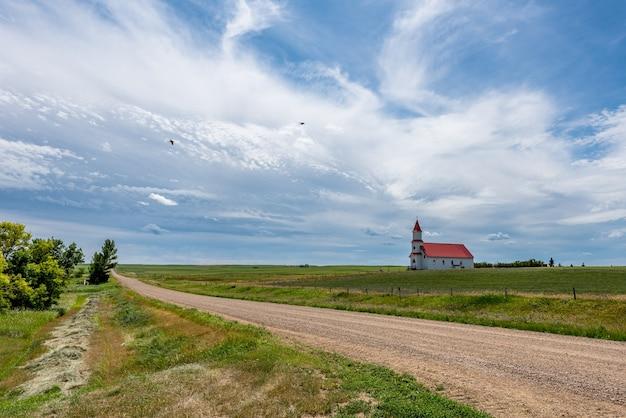 カナダ、サスカチュワン州ビリマンの歴史的な聖マルティンスローマカトリック教会に通じる国の砂利道を飛んでいる鳥