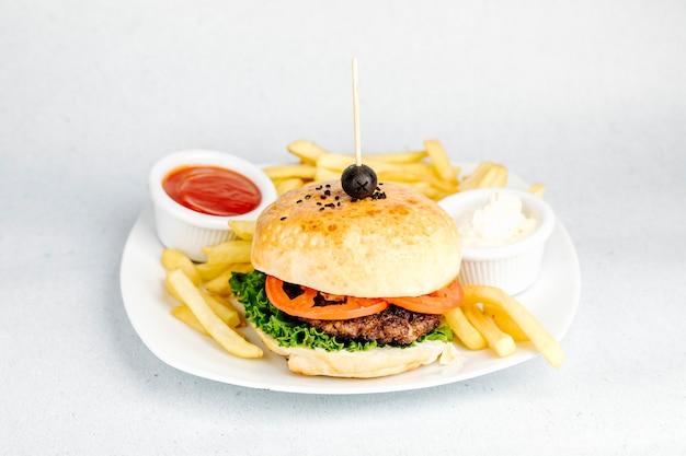 Биргер с мясом и помидорами, с кетчупом, майонезом и картофелем.