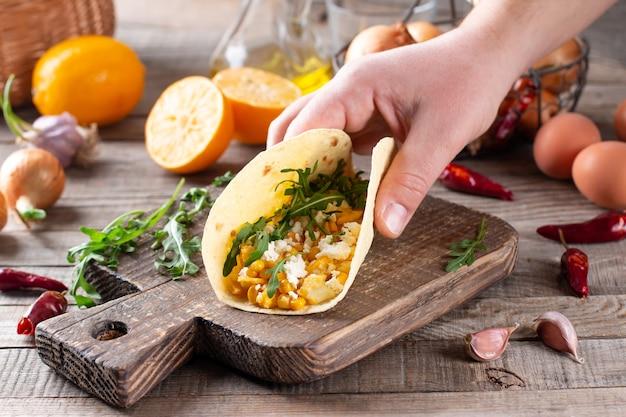 木製のテーブルに卵、トウモロコシ、チーズ、野菜とビリアタコス