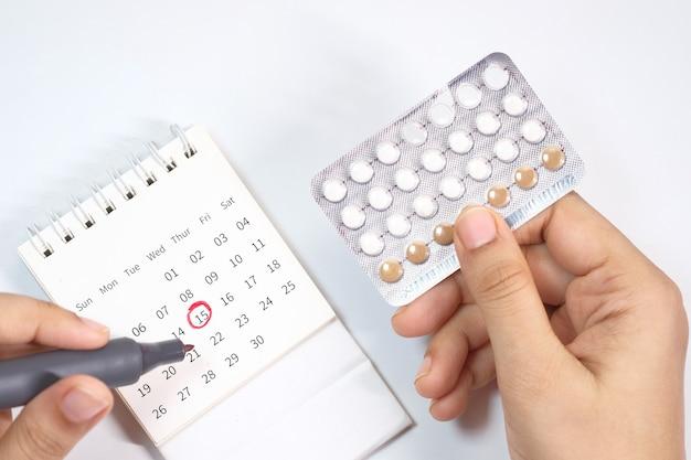 Противозачаточные таблетки, календарь и блокнот на столе.
