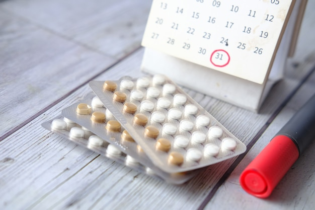 Birth control pills  calendar and notepad on table