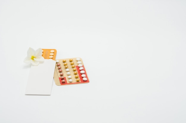 Birth control pills or contraceptive pill with paper case and white flower on white background. family planning concept. hormone replacement therapy. hormonal acne treatment with anti-androgenic pill.