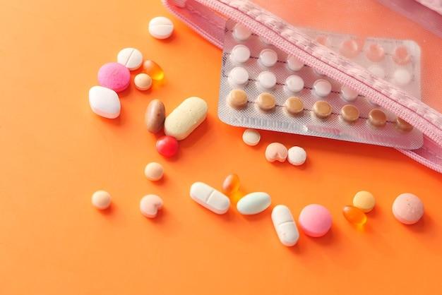 オレンジ色の背景に経口避妊薬、クローズアップ。