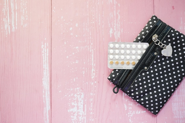 Birth control pills and a small bag on pink surface top down
