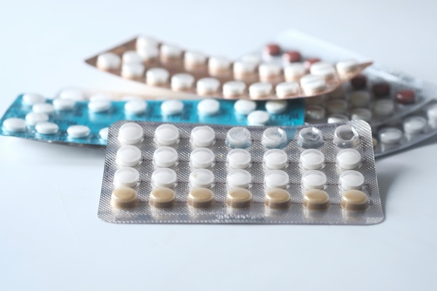 Birth control pills on wooden background, close up .