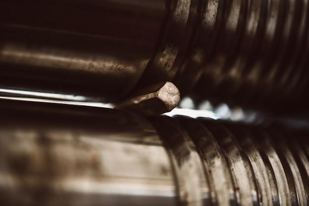 디테일의 탄생. 보석 워크샵에서 공예 압연 기계에 금속 세부 사항을 만드는 여성 금세공인