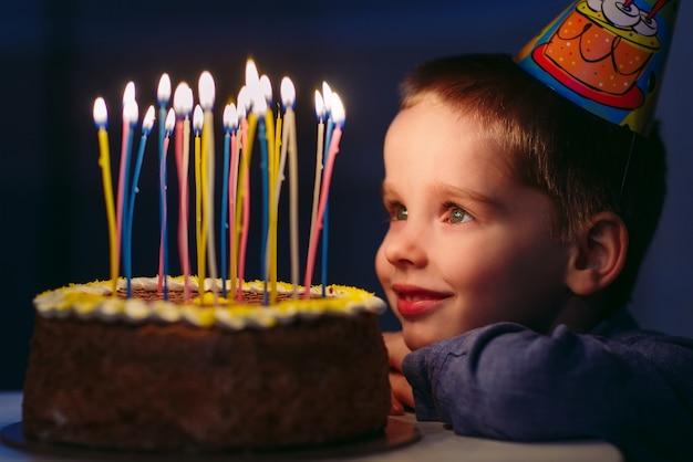 День рождения. маленький мальчик выдувает свечи на плите.