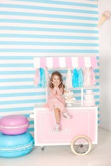 День рождения и концепция счастья - счастливая маленькая девочка сидит на тележке с мороженым и сладостями