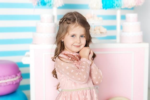 День рождения и концепция счастья - счастливая маленькая девочка с конфетами