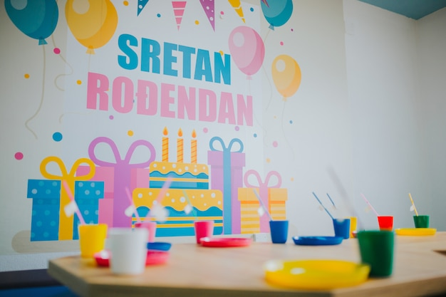День рождения в детском саду с красочной посудой на деревянных столиках