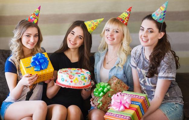 誕生日、誕生日の女性がプレゼントとケーキでポーズ。