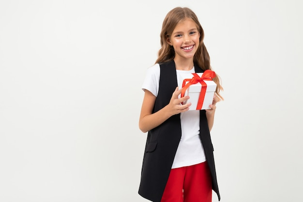 Birthday . attractive smiling girl with a gift with a red ribbon in her hands on a white  with copyspace