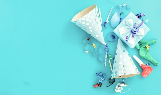 Birthday balloon background with gift box, colorful party streamers, confetti and birthday party hats on blue