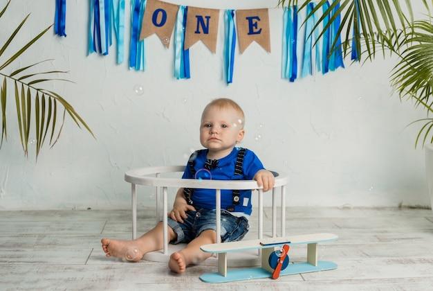 A birthday boy celebrates his first birthday on a white background