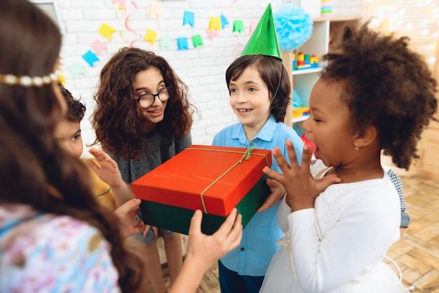 Birthday boy in festive hat receives gift at birthday party.
